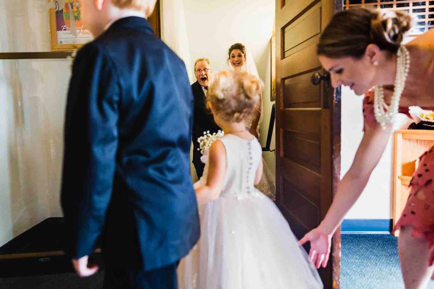 bride and her dad laugh at the flower girl and ring bearer, just before they walk up the aisle at her wedding