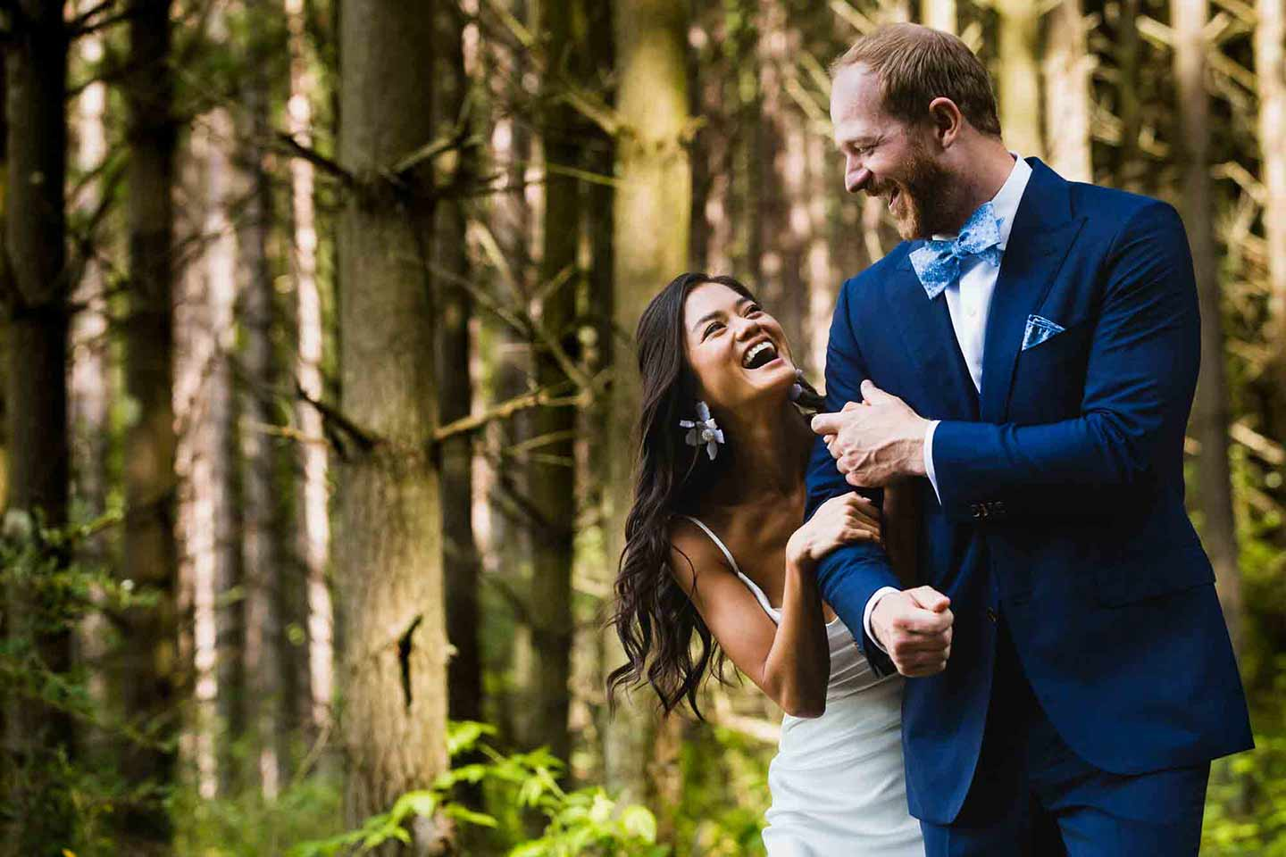 bride and groom walk together laughing in the woods