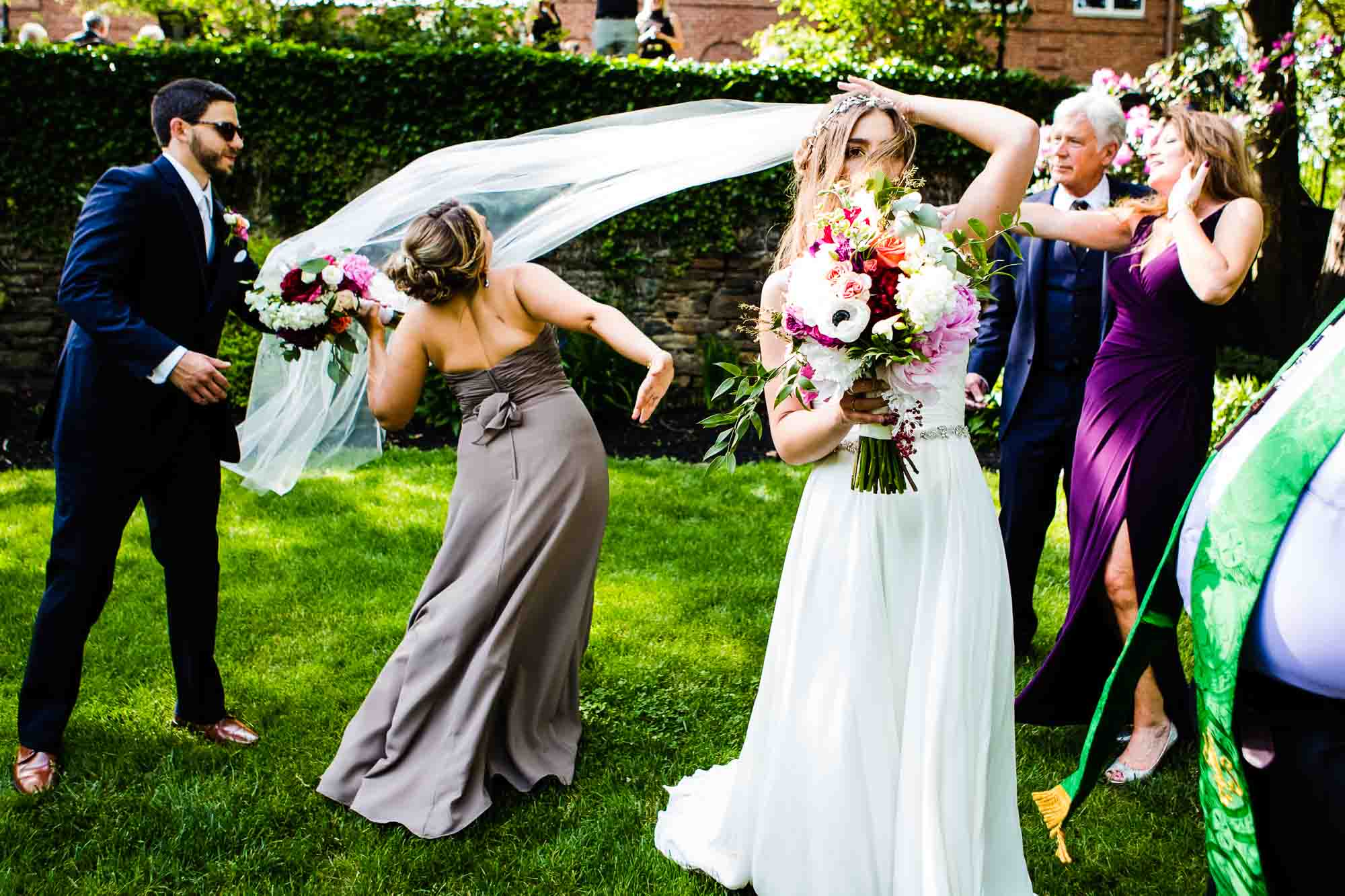 bride's veil flies in the wind and bridesmaid runs into it in awkward movement, while wedding guests look on