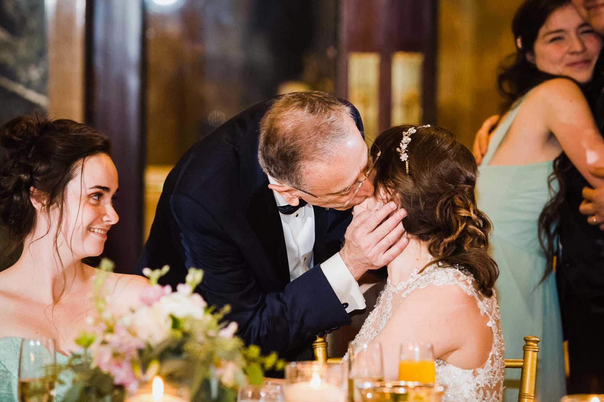 father of the bride kisses his daughter gently on the cheek while a bridesmaid smiles at them