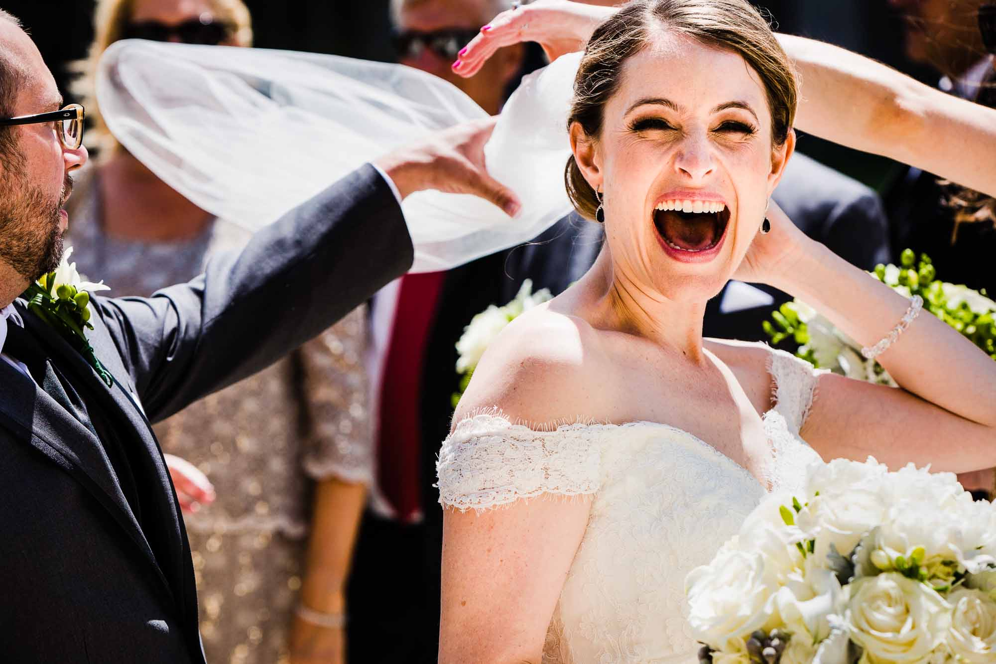 bride laughing while veil flies up in the air due to windy day