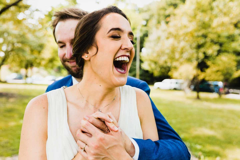 bride laughs in a genuine fun way as her groom is hugging her from behind
