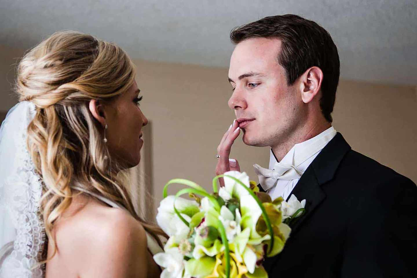 bride touching her groom's lips in an emotional moment during their First Look portraits on their wedding day