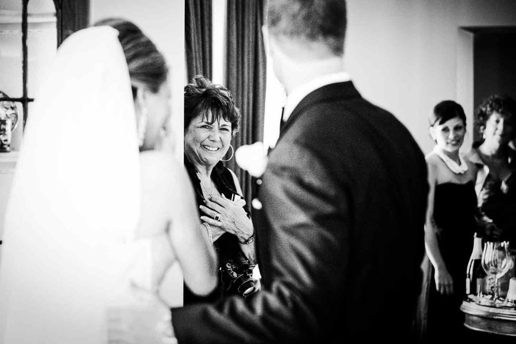 black and white picture of mother of the bride holding hands across her chest and crying as she looks at bride and groom