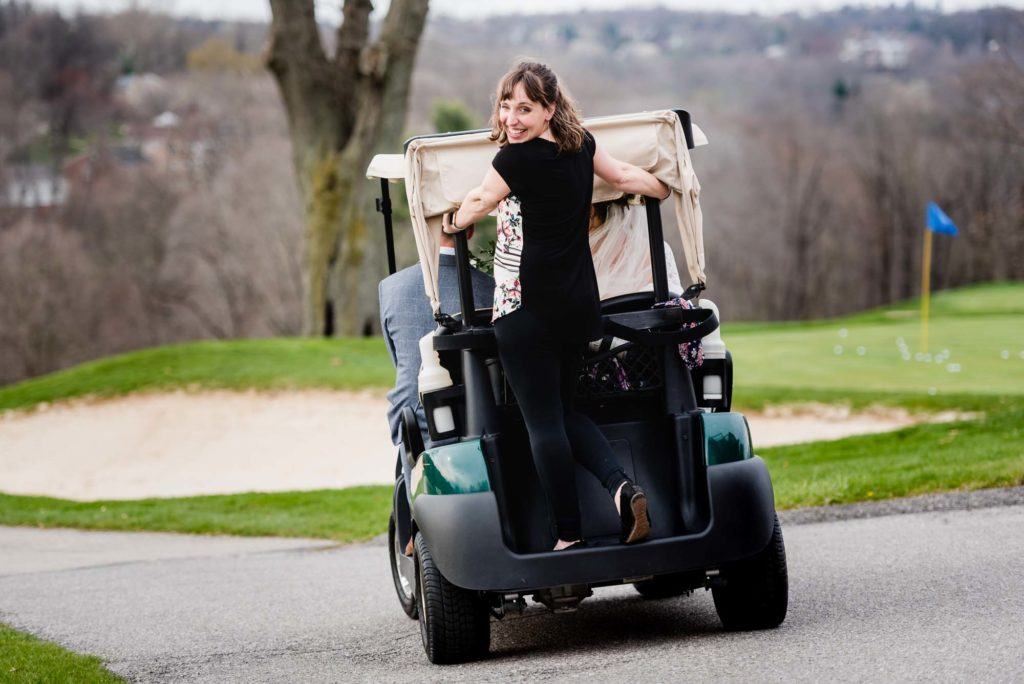 photographer rides on back of golf cart with bride and groom, smiling