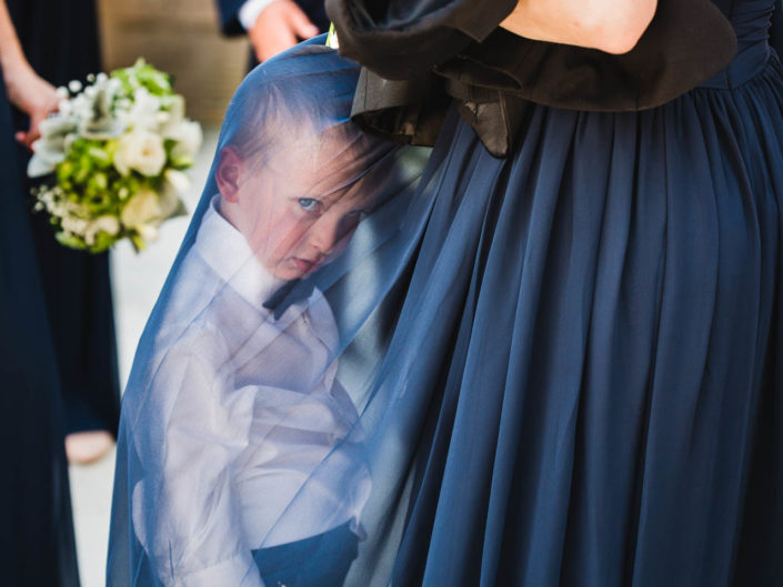 tired grumpy ring bearer slumps under a bridesmaid's sheer dress with a funny expression