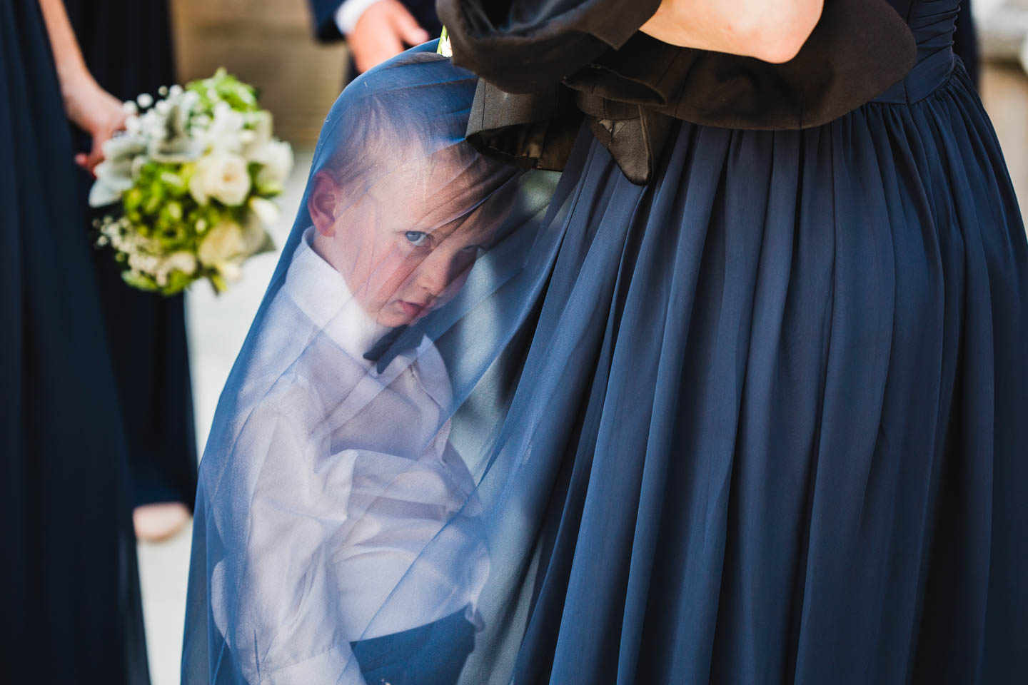grumpy ring bearer hides under a bridesmaid's dress at the bride's photo session on their wedding day