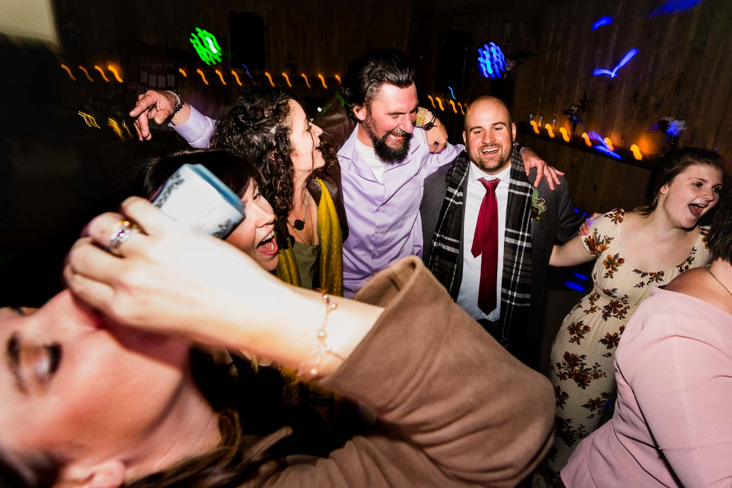 candid picture of guests dancing wildly at a wedding reception